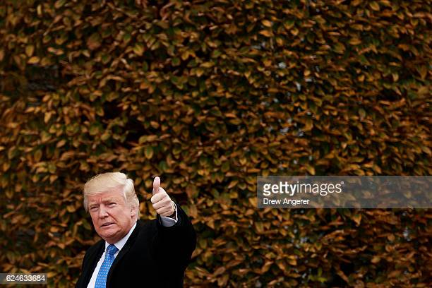 Presidentelect Donald Trump gives a thumbs up as he arrives at Trump International Golf Club for a day of meetings November 20 2016 in Bedminster...