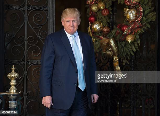 US Presidentelect Donald Trump greets the media after meeting with David Rubenstein cofounder of Carlyle Group December 28 2016 at MaraLago in Palm...