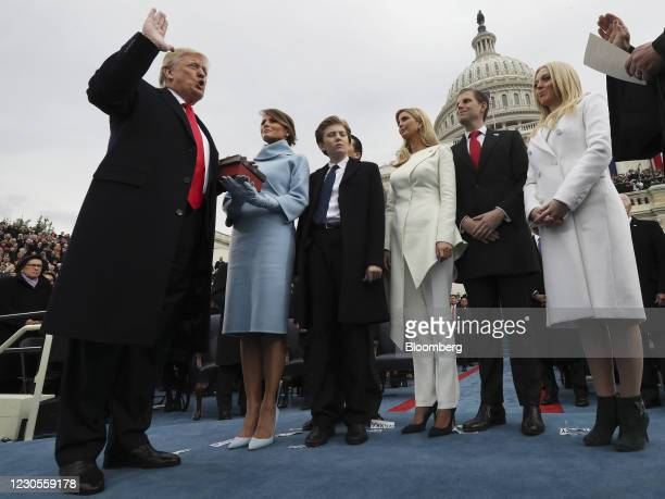 President-elect Donald Trump, left, takes the oath of office as U.S. First Lady-elect Melania Trump and family stand during the 58th presidential...