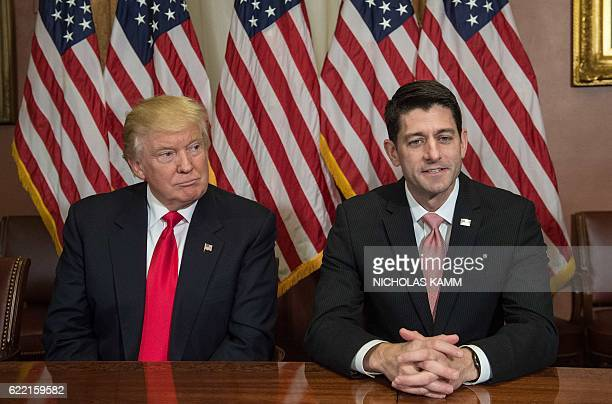 US Presidentelect Donald Trump listens to House Speaker Paul Ryan talk to the press at the US Capitol in Washington DC on November 10 2016 / AFP /...