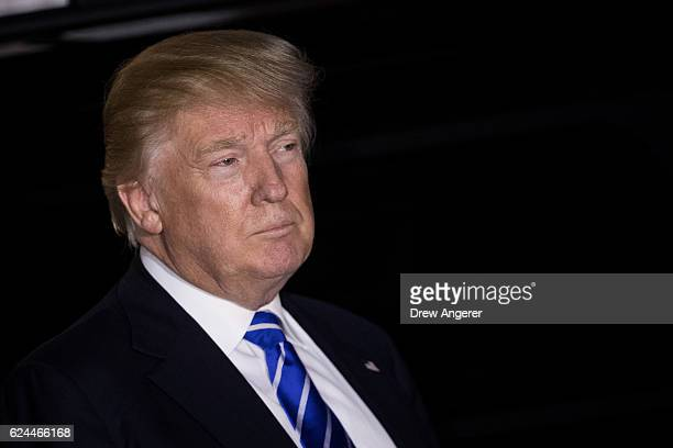 Presidentelect Donald Trump listens to questions from the press as he exits the clubhouse after a day of meetings at Trump International Golf Club...