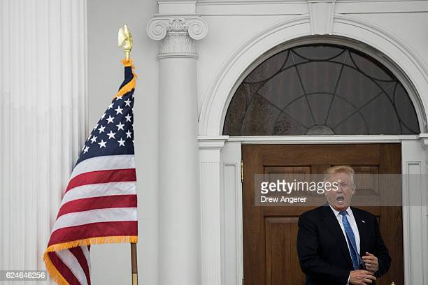 Presidentelect Donald Trump responds to a question outside the clubhouse following his meeting with Peter Kirsanow attorney and member of the US...
