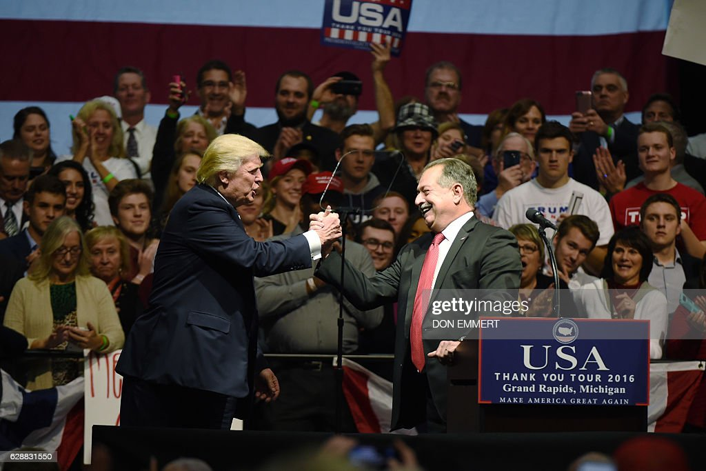 US President-elect Donald Trump shakes hands with Australian businessman Andrew Liveris during the USA Thank You Tour December 9, 2016 in Grand Rapids, Michigan. / AFP / DON