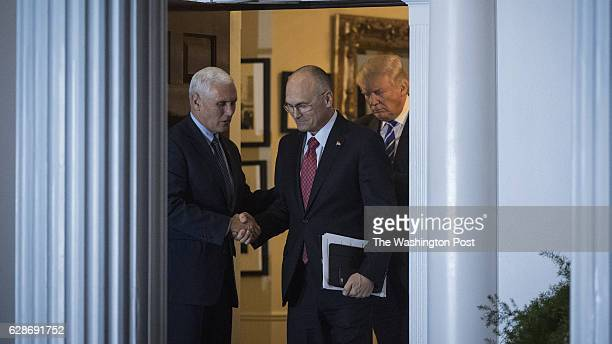 Presidentelect Donald Trump Vice Presidentelect Mike Pence and Andy Puzder chief executive of CKE Restaurants walk out at the clubhouse at Trump...