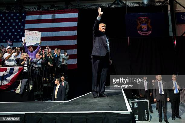 Presidentelect Donald Trump waves to the crowd as he arrives onstage at the DeltaPlex Arena December 9 2016 in Grand Rapids Michigan Presidentelect...