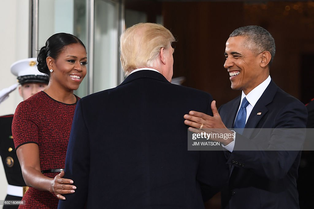 TOPSHOT - President-elect Donald Trump(C)is greeted by US President Barack Obama and First Lady Michelle Obama(L) as he arrives at the White House in Washington, DC January 20, 2017. / AFP / JIM