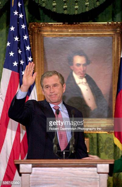 US PresidentElect George W Bush waves goodbye to the people of Texas during his farewell speech as Governor of the state Behind him is a portrait of...