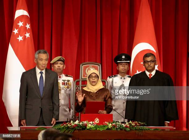 Presidentelect Halimah Yacob takes the oath of office while flanked by Singapore Prime Minister Lee Hsien Loong and Chief Justice Sundaresh Menon...