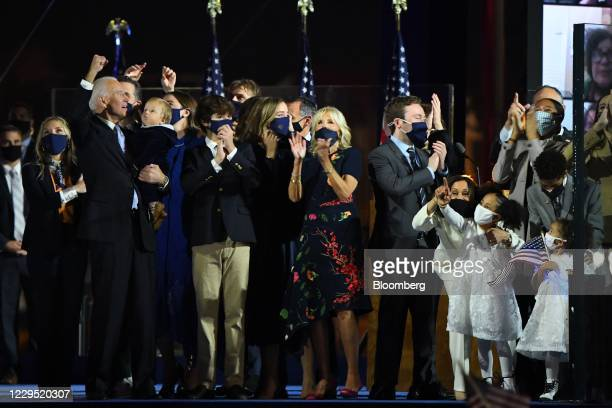 President-elect Joe Biden, left, and U.S. Vice President-elect Kamala Harris, right, along with their families watch a fireworks display after...
