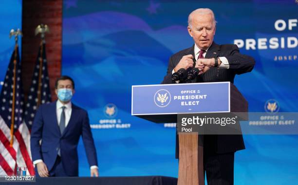President-elect Joe Biden looks at his watch as former Democratic presidential candidate Pete Buttigieg arrives behind him during a news conference...