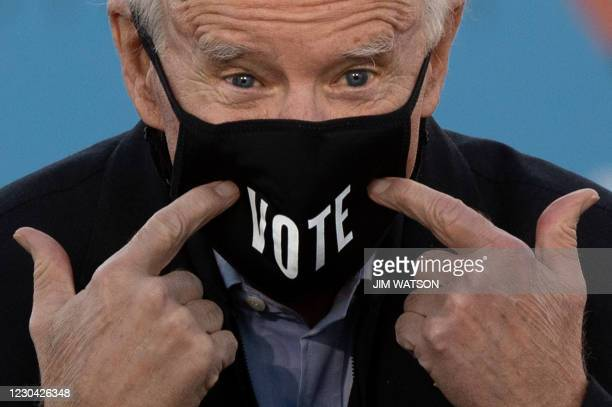 "President-elect Joe Biden points to his face mask with the word ""Vote"" printed on it during a rally outside Center Parc Stadium in Atlanta, Georgia,..."