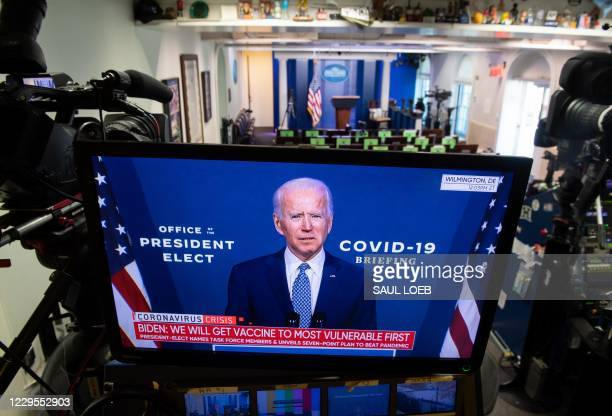 President-elect Joe Biden speaks about coronavirus as he appears on a television in the Brady Press Briefing Room of the White House in Washington,...