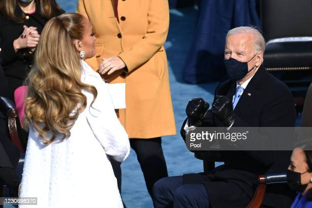 President-elect Joe Biden talks to US singer Jennifer Lopez during the 59th Presidential Inauguration at the U.S. Capitol on January 20, 2021 in...