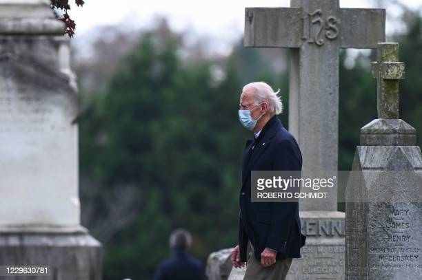 President-elect Joe Biden walks past tombstones after leaving the St. Joseph on the Brandywine Catholic Church after attending Mass in Wilmington,...