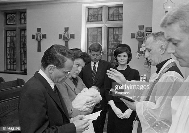 Presidentelect John F Kennedy and wife Jackie stand by as their infant son John Jr is christened at Georgetown Hospital His godparents are Mr and Mrs...