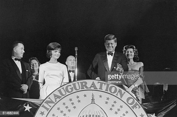 President-elect John F. Kennedy stands with wife Jackie and smiles at the applause given to him at the pre-Inaugural gala. Also on the podium is...