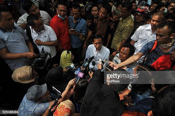 Presidentelect Joko Widodo answers a reporters questions during a visit at a second hand market in Surakarta Central Java Indonesia on July 26...