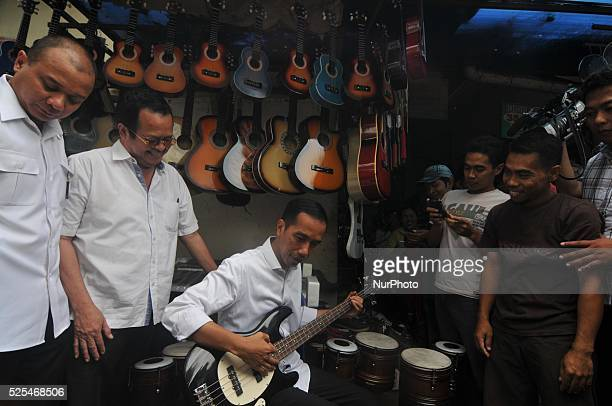 Presidentelect Joko Widodo Presidentelect Joko Widodo tryi to playing a guitar that sold during a visit at a second hand market in Surakarta Central...