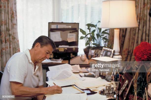 Presidentelect Ronald Reagan sitting at desk writing inaugural speech at home