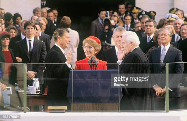 President-elect Ronald Reagan takes the oath of office during inauguration ceremonies in Washington, DC. His wife, Nancy, is holding the Bible and...