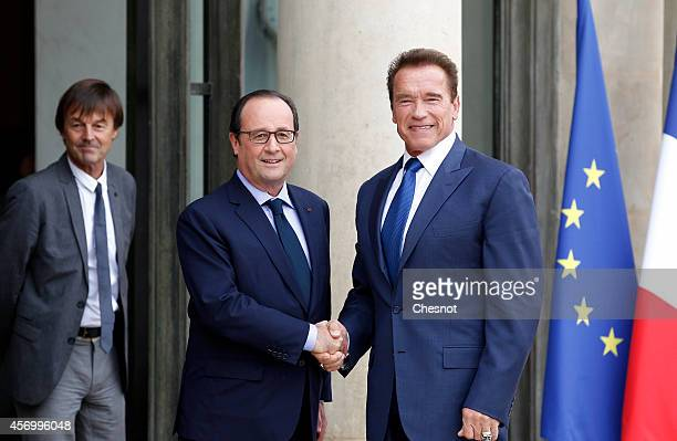 Presidential advisor Nicolas Hulot stands as French president Francois Hollande welcomes US actor former California state governor and founding chair...