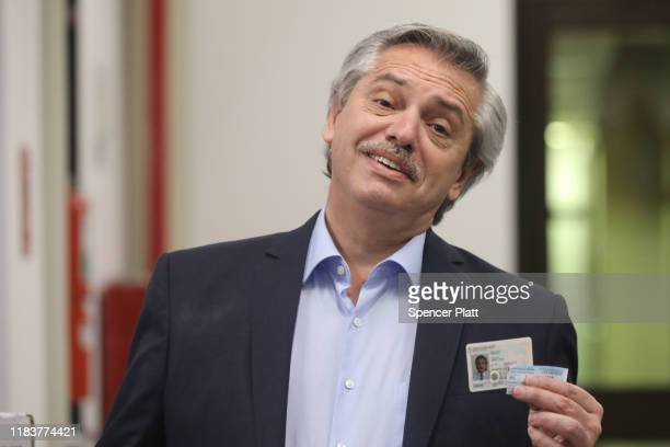 Presidential candidate Alberto Fernandez of 'Frente de Todos' poses with his ID after casting his vote during the presidential elections in Argentina...