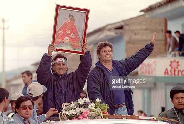 Presidential candidate Alejandro Toledo accompanied by vice presidential candidate Raul Diez Canseco right greets supporters as he carries a picture...