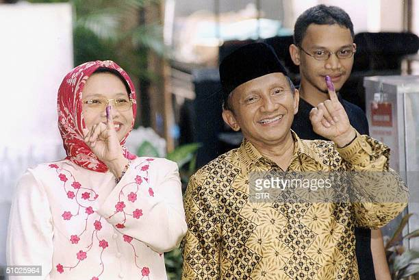 Presidential candidate Amien Rais and his wife Kusnariyati Sri Rahayu hold up their inkcovered fingers to prove they have voted in the country's...