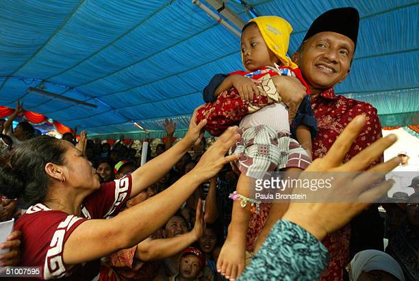 Presidential candidate Amien Rais holds a child while campaigning in Cengkareng June 29 a slum area west of Jakarta Indonesia Candidates have entered...