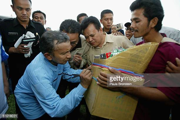 Presidential candidate Amien Rais signs his autograph on the box of a cigarette vendor after a friendly soccer match between Amien's party the...