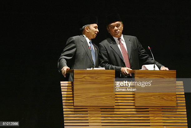Presidential candidate Amien Rais whispers to his respective running mates Siswono Yudhohusodo during televised presidential dialogue on June 30 in...