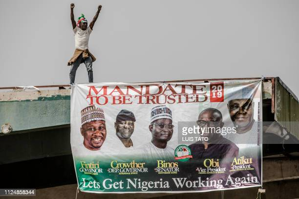 A presidential candidate Atiku Abubakar's supporter celebrates near a candidate's poster on a roof before the start of the opposition Peoples...