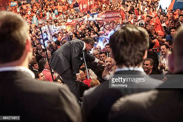 Presidential candidate Daniel Scioli center reaches out to bump fists with a supporter at his campaign headquarters on election night in Buenos Aires...