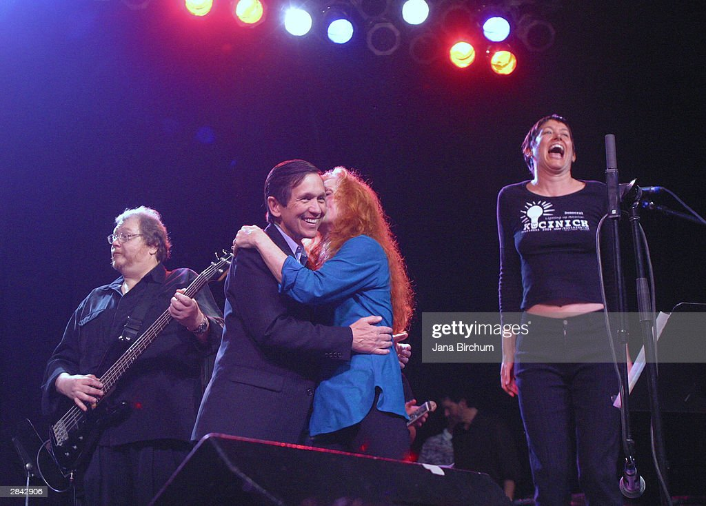 Presidential candidate Dennis Kucinich gets a kiss from musician Bonnie Raitt as Michelle Shocked sings at a fundraiser January 3, 2004 in Austin, Texas. The fundraiser was designed to elevate the name of Kucinich, who has received little recognition among voters outside his home state.