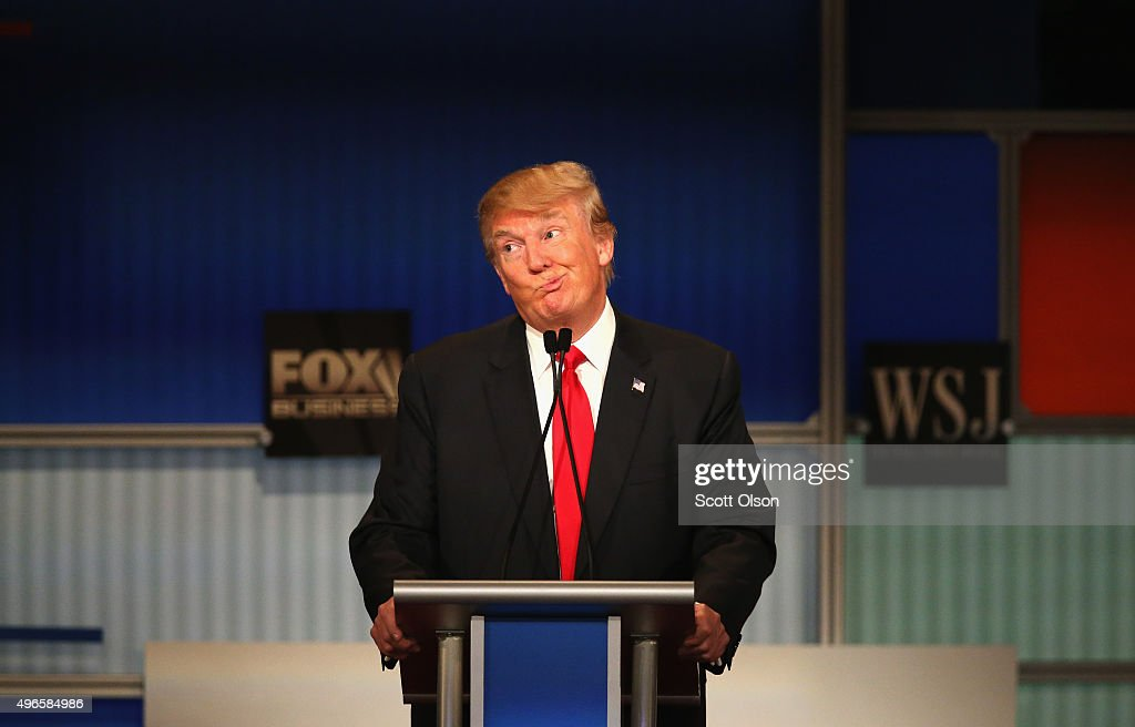 Presidential candidate Donald Trump gestures after Carly Fiorina says she met with Russian President Putin at a one on one meeting, during the Republican Presidential Debate sponsored by Fox Business and the Wall Street Journal at the Milwaukee Theatre November 10, 2015 in Milwaukee, Wisconsin. The fourth Republican debate is held in two parts, one main debate for the top eight candidates, and another for four other candidates lower in the current polls.