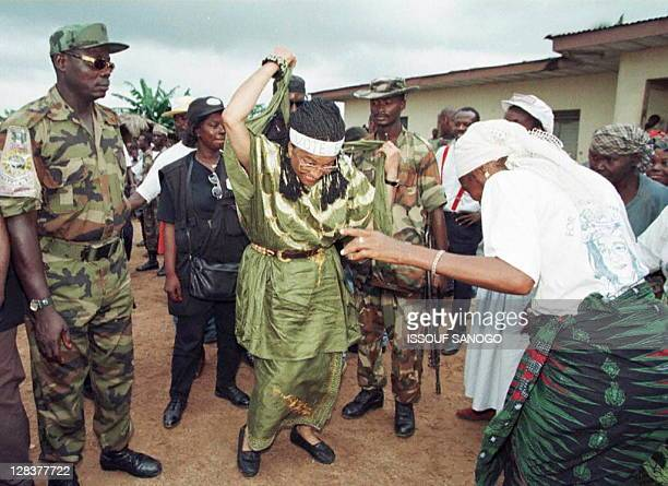 Presidential candidate Ellen JohnsonSirleaf dancing with a woman supporter on campaign trail at the Moulton Corner displaced center in Monrovia's...