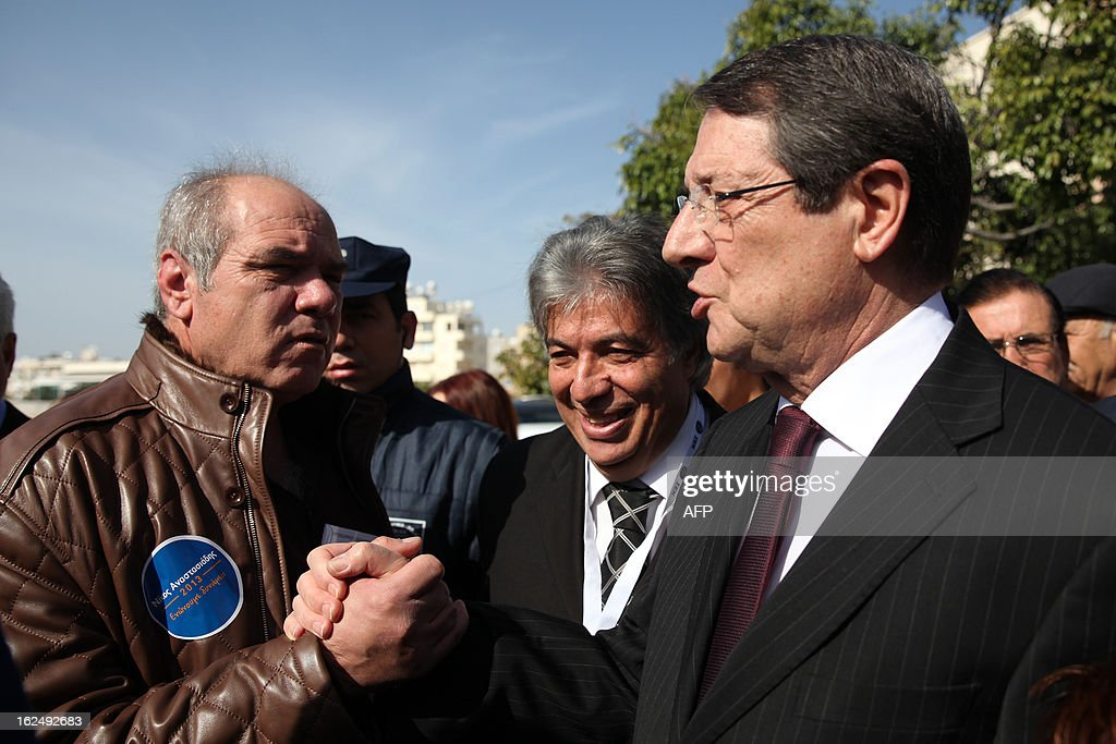Presidential candidate for the Democratic Rally of Cyprus (DISY) party, Nicos Anastasiades (R) greets people as he leaves the polling station after voting in the second round of Cyprus' presidential election on February 24, 2013 in Limassol. Cypriots began voting in a crucial left-right presidential runoff to elect a new leader to seal a much needed rescue package for the EU state on the brink of financial ruin.