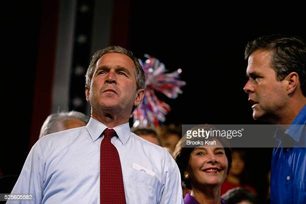Presidential candidate George W Bush converses with his brother Jeb Bush during his campaign Laura Bush stands behind them George W Bush is running...