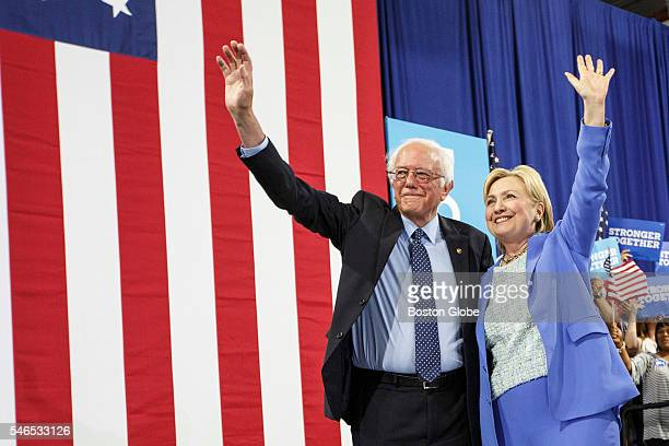 S Presidential candidate Hillary Clinton and US Senator and former presidential candidate Bernie Sanders wave from the stage during a campaign event...