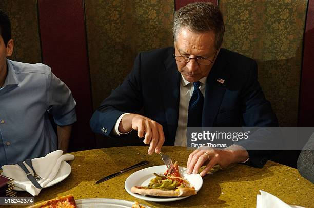 Presidential Candidate John Kasich eats a piece of pizza at Gino's Pizzeria and Restaurant on March 30 2016 in the Queens borough of New York City...