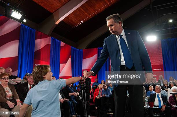 Presidential Candidate John Kasich fist bumps a young fan during a town hall meeting at St Helen's Roman Catholic Church on March 30 2016 in the...