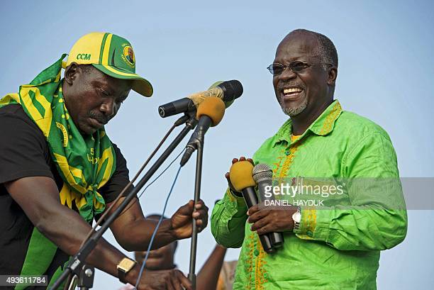 Presidential candidate John Magufuli laughs as microphones are set up during a ruling Chama Cha Mapinduzi rally in Dar es Salaam Tanzania on October...