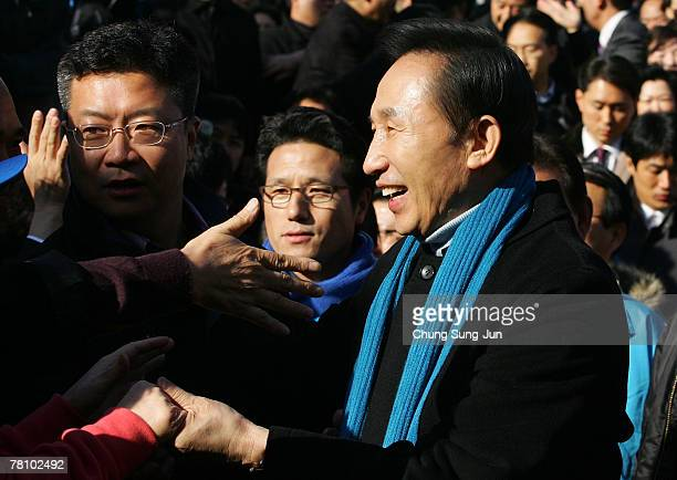 Presidential candidate Lee MyungBak of the conservative main opposition Grand National Party shakes hands with his supporters during presidential...
