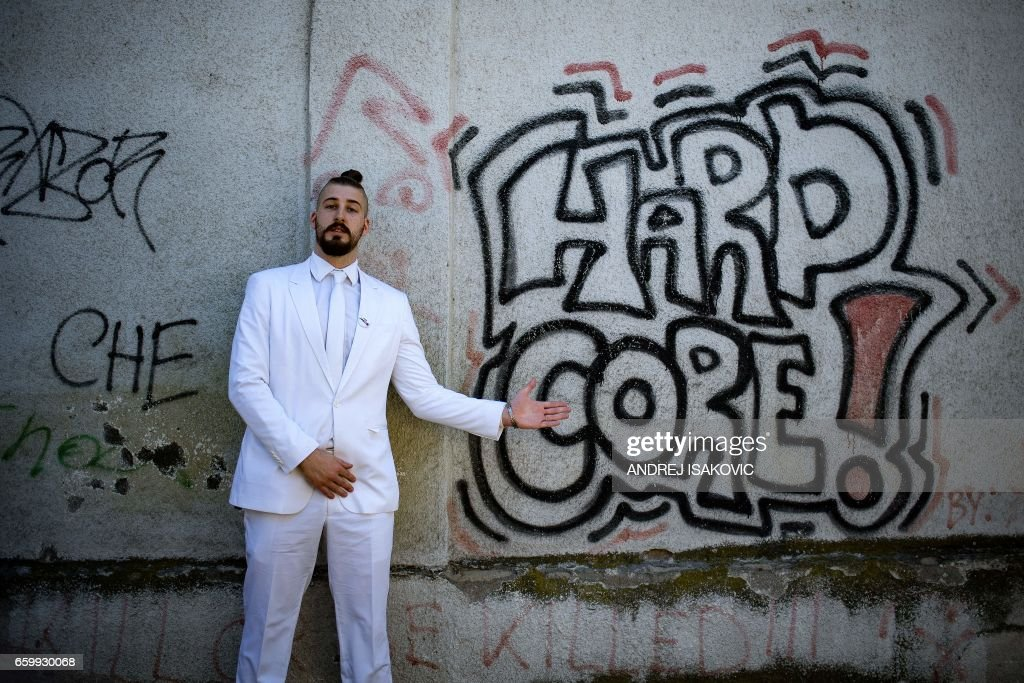 Presidential candidate, Luka Maksimovic alias Beli, a 25-year-old satirist, poses in front of a graffiti in the Serbian town of Mladenovac on March 21, 2017. Beli campaigns in a Borat-style white suit, sports a samurai-style ponytail and hipster beard, touts a manifesto studded with lunatic pledges and uses a made-up name that mocks politics as the circus of greed. Maksimovic, a media and communication student, chose the name of Ljubisa Preletacevic -- nicknamed 'Beli' (White) -- as the fictitious monicker for his candidate. /