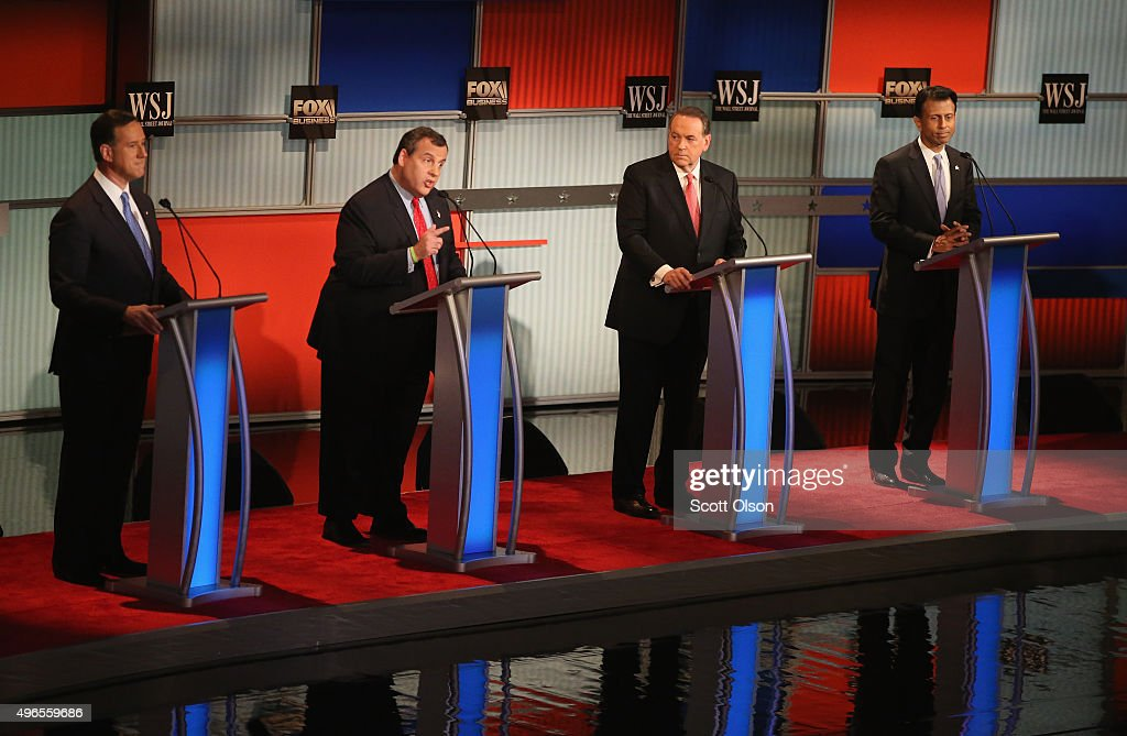 Presidential candidate New Jersey Gov. Chris Christie (2nd L) speaks while Rick Santorum, Mike Huckabee, and Louisiana Gov. Bobby Jindal look on during the Republican Presidential Debate sponsored by Fox Business and the Wall Street Journal at the Milwaukee Theatre November 10, 2015 in Milwaukee, Wisconsin. The fourth Republican debate is held in two parts, one main debate for the top eight candidates, and another for four other candidates lower in the current polls.
