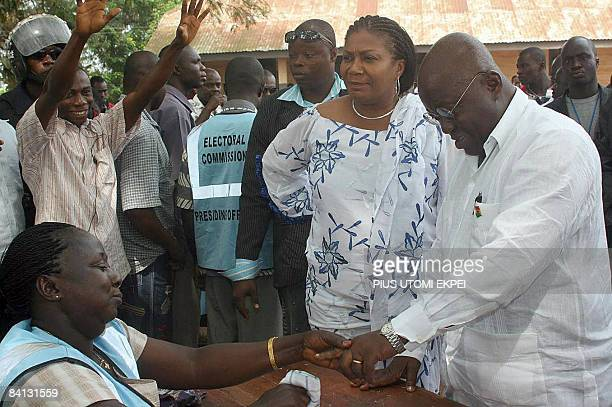Presidential candidate of the New Patriotic Party Nana AkufoAddo accompanied by his wife Rebecca prints his finger before casting his ballot on...