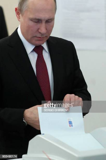 Presidential candidate President Vladimir Putin casts his ballot at a polling station during Russia's presidential election in Moscow on March 18...