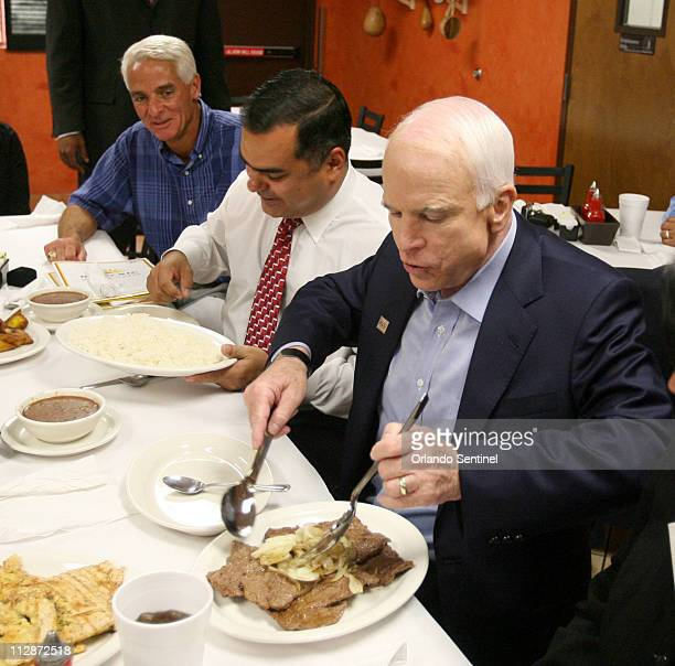 GOP presidential candidate Sen John McCain tries a dish with Ramon Ojeda president of the Hispanic Chamber of Commerce of Metro Orlando center and...