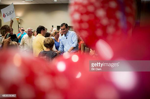 Presidential candidate Sen. Ted Cruz seen through red balloons, arrives to speak to supporters during the Cruz campaign bus tour rally in Pelham,...