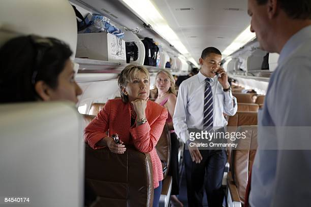 Presidential candidate Senator Barack Obama and Senator Hillary Rodham Clinton work their cellphones and chat together on his campaign plane at...